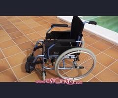 Silla de ruedas y barandila de cama